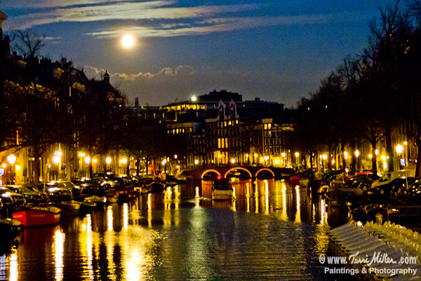 The full moon rising over one of Amsterdam's canals